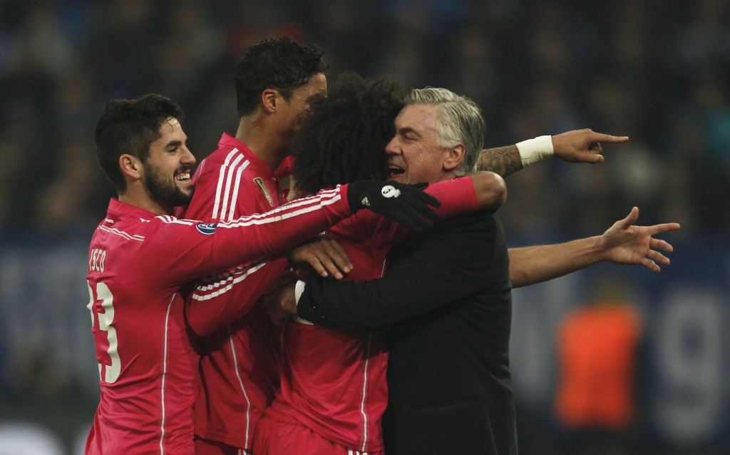 Real Madrid's Isco, Varane and Marcelo celebrate with coach Ancelotti after scoring a goal against Schalke 04 during their Champions League Round of 16 first leg soccer match in Gelsenkirchen